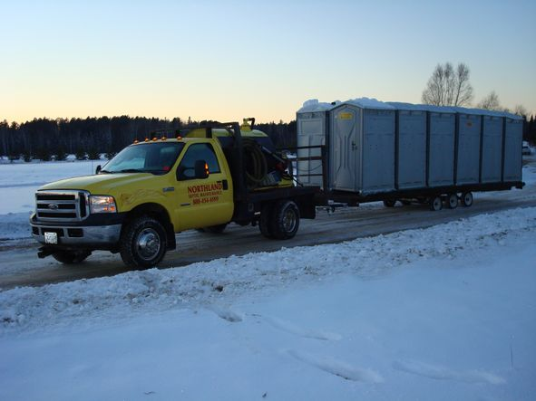 Northland truck transporting several portable toilets