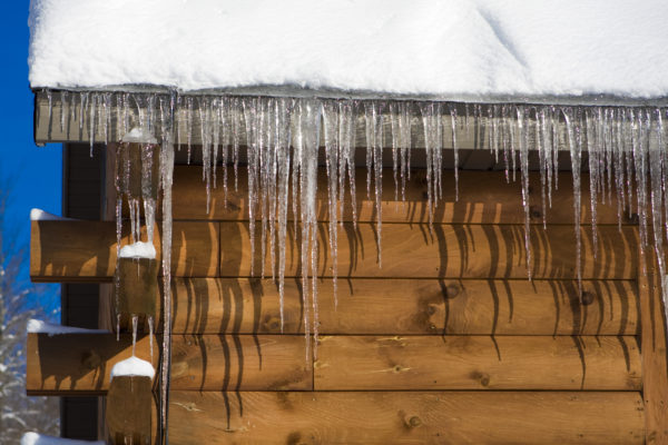 Icicles hanging from a snowy cabin roof
